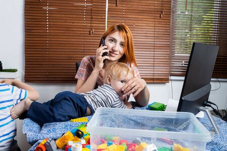 A young man dad talking on the phone and trying to work at a computer at a remote work during the period of self-isolation in connection with the coronovirus pandemic, soft focus. Work from home with young children Stock Photo