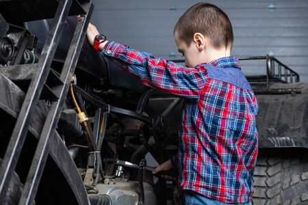 A young boy, a young auto worker, repairing a motorcycle suspension with   pneumatic ratchet wrench  in the garage of a service station. A child learns the mechanics changing profession in auto repair service. Фото со стока