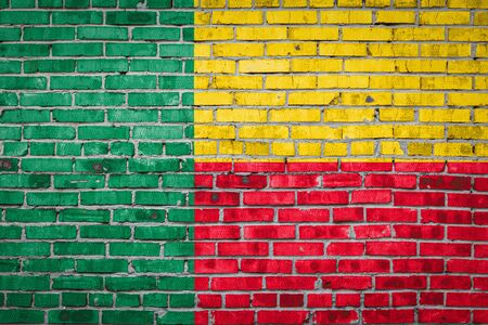 National flag of Benin depicting in paint colors on an old brick wall. Flag  banner on brick wall background. Stock Photo