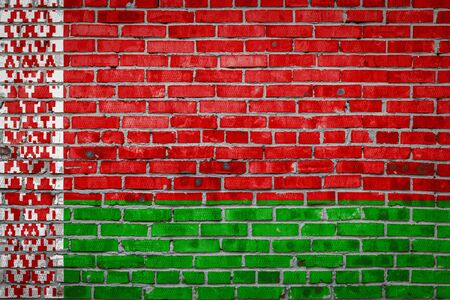 National flag of Belarus  depicting in paint colors on an old brick wall. Flag  banner on brick wall background.