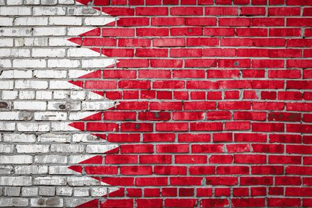 National flag of Bahrain  depicting in paint colors on an old brick wall. Flag  banner on brick wall background. Stock Photo