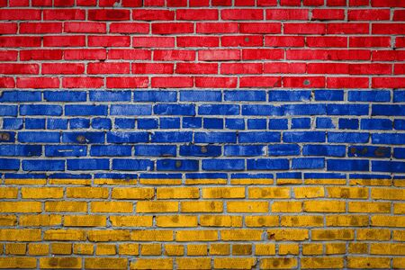 National flag of Armenia  depicting in paint colors on an old brick wall. Flag  banner on brick wall background.