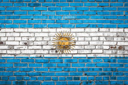 National flag of Argentina  depicting in paint colors on an old brick wall. Flag  banner on brick wall background. Stock Photo