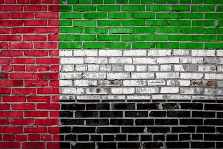National flag of United Arab Emirates depicting in paint colors on an old brick wall. Flag  banner on brick wall background.