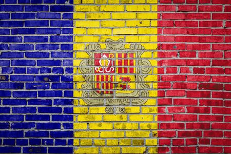 National flag of Andorra  depicting in paint colors on an old brick wall. Flag  banner on brick wall background.
