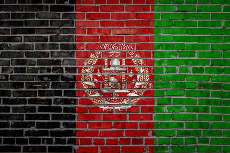 National flag of Afghanistan depicting in paint colors on an old brick wall. Flag  banner on brick wall background.