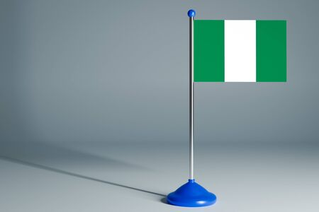 The 3d rendering  realistic national flag of Nigeria on steel pole on gray isolated background.  Blank table flag , suitable for design, mockup Stock Photo