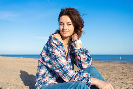 Fashion lifestyle portrait of young trendy woman dressed in shirt and jeans laughing, smiling, posing on the beach Foto de archivo