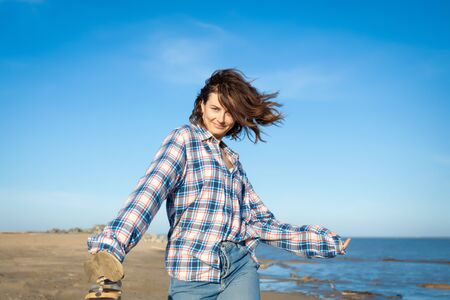 Fashion lifestyle portrait of young trendy woman dressed in shirt and jeans laughing, smiling, posing n the beach