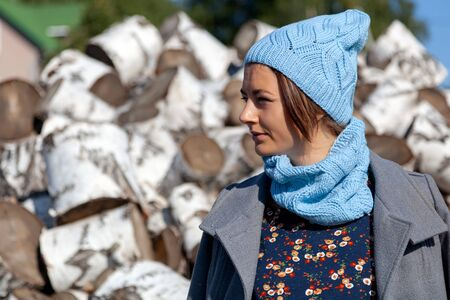 Portrait of a young cheerful woman in a knitted hat,  jacket, pretty dress and boots, smiles cute and sits on birch logs. The concept of rustic style and life in ancient times Stock Photo