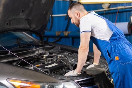 Handsome young male auto mechanic in special uniform clothes  looking for breakdown and repairing under the hood in the car engine in a car workshop