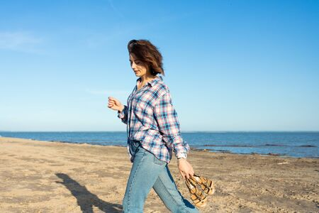 Outdoor atmospheric lifestyle photo of young beautiful darkhaired woman in shirt and jeans in on the beach, in the background the sea with sunset.