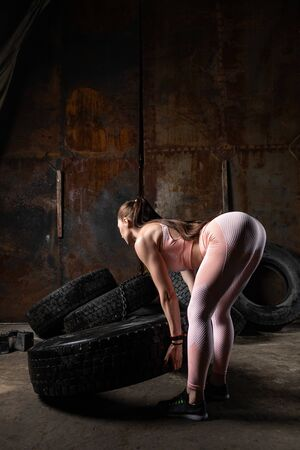 A sporty woman in a pink top and leggings doing sit-ups, deadlift with a weight tyre in the sports gym garage. Technique of squats with weight