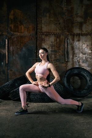 A young woman model in a sporty short top and gym leggings makes lunges  by the feet forward, hands are held out to the at the waist   in an old garage, against the background of tires