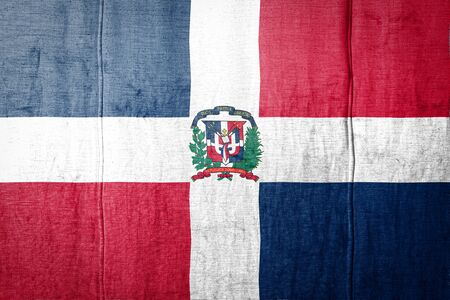 National flag of Dominicana depicting in paint colors on old clothl. Flag banner on fabric texture background.