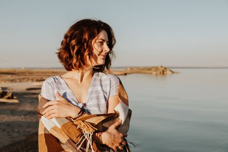 Concept of summer holidays at sea and live style. Young woman in blue dress with a plaid posing and walking against the backdrop of a sea. Photos on summer vacation