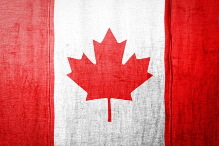 National flag of  Canada  depicting in paint colors on old textile. Flag  banner on  fabric texture background.