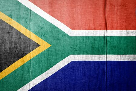 National flag of South African Republic depicting in paint colors on old textile. Flag  banner on  fabric texture background.