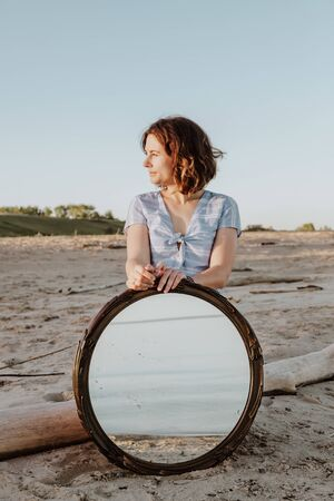 Outdoor atmospheric lifestyle photo of young beautiful  darkhaired woman in summer dress   posing on the beach in the reflection of the mirror.Conceptual photo with a mirror. Stock Photo