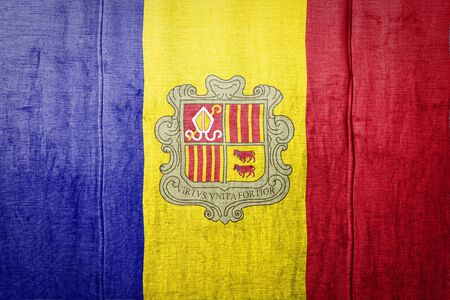 National flag of Andorra depicting in paint colors on old textile. Flag banner on fabric texture background.