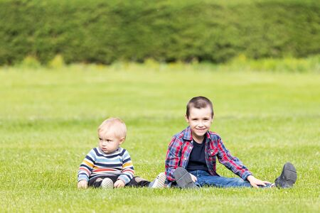 Two cheerful boy brothers of different ages play fun, sit on the grass on a warm summer day. The concept of friendship of brothers and happy childhood. Stock Photo
