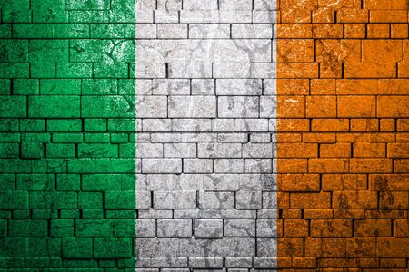 National flag of Ireland on brick  wall background.The concept of national pride and symbol of the country. Flag  banner on  stone texture background. Banque d'images