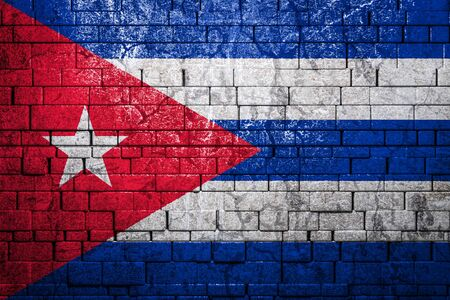 National flag of Cuba on brick wall background.The concept of national pride and symbol of the country. Flag banner on stone texture background.