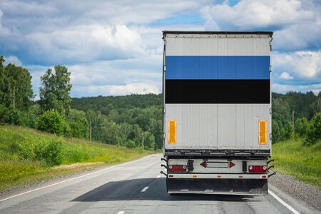 A truck with the national flag of Estonia depicted on the back door carries goods to another country along the highway. Concept of export-import,transportation, national delivery of goods
