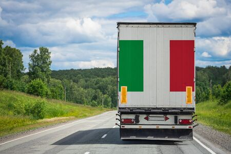 A truck with the national flag of Italy depicted on the back door carries goods to another country along the highway. Concept of export-import,transportation, national delivery of goods