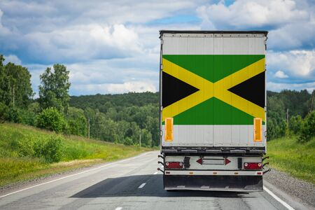 A  truck with the national flag of Jamaica depicted on the back door carries goods to another country along the highway. Concept of export-import,transportation, national delivery of goods