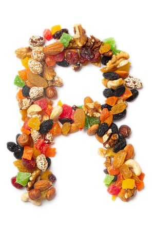 Letter R of the English alphabet from a mixture of hazelnuts, almonds, walnuts, cashews, seeds, raisins, candied fruit on a white isolated background. Food pattern made from nuts.