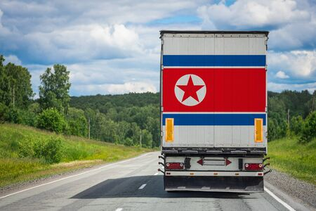 A  truck with the national flag of North Korea depicted on the back door carries goods to another country along the highway. Concept of export-import,transportation, national delivery of goods