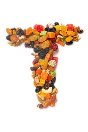 Letter T of the English alphabet from a mixture of hazelnuts, almonds, walnuts, cashews, seeds, raisins, candied fruit on a white isolated background. Food pattern made from nuts.