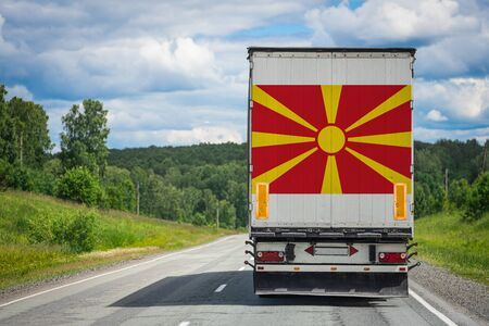 A truck with the national flag of Macedonia depicted on the back door carries goods to another country along the highway. Concept of export-import,transportation, national delivery of goods