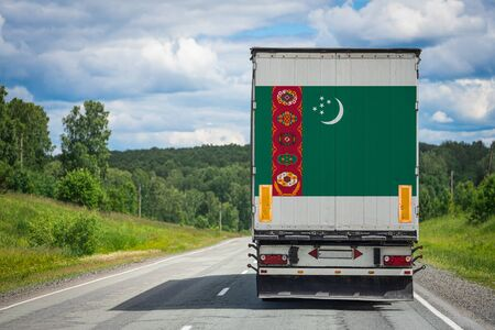 A  truck with the national flag of Turkmenistan depicted on the back door carries goods to another country along the highway. Concept of export-import,transportation, national delivery of goods