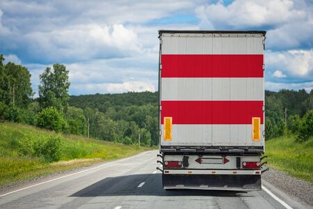 A  truck with the national flag of Austria depicted on the back door carries goods to another country along the highway. Concept of export-import,transportation, national delivery of goods 免版税图像 - 150288162