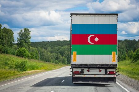 A truck with the national flag of Azerbaijan depicted on the back door carries goods to another country along the highway. Concept of export-import,transportation, national delivery of goods