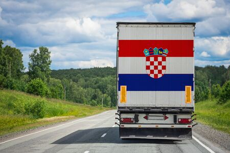 A truck with the national flag of Croatia depicted on the back door carries goods to another country along the highway. Concept of export-import,transportation, national delivery of goods