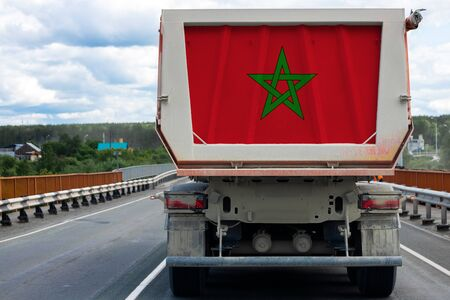 Big dirty truck with the national flag of Morocco moving on the highway, against the background of the village and forest landscape. Concept of export-import,transportation, national delivery of goods
