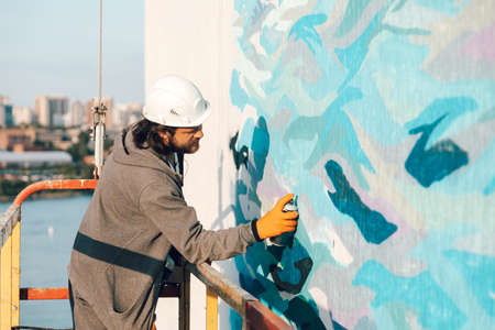 Graffiti artist paints a white wall at high altitude in waves. Permitted graffiti by all the rules