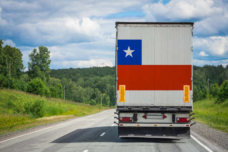 A  truck with the national flag of Chile depicted on the back door carries goods to another country along the highway. Concept of export-import,transportation, national delivery of goods
