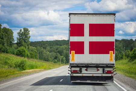 A  truck with the national flag of Denmark depicted on the back door carries goods to another country along the highway. Concept of export-import,transportation, national delivery of goods