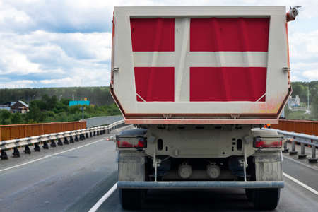 Big  truck with the national flag of  Denmark moving on the highway, against the background of the village and forest landscape. Concept of export-import,transportation, national delivery of goods Фото со стока