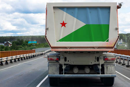 Big  truck with the national flag of  Djibouti moving on the highway, against the background of the village and forest landscape. Concept of export-import,transportation, national delivery of goods