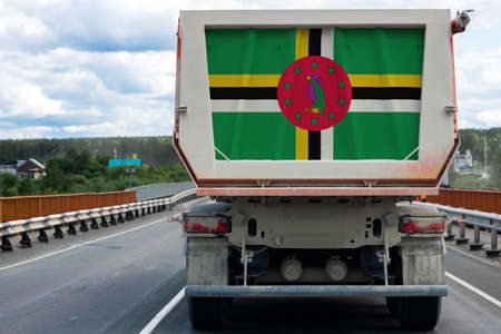 Big  truck with the national flag of Dominica moving on the highway, against the background of the village and forest landscape. Concept of export-import,transportation, national delivery of goods