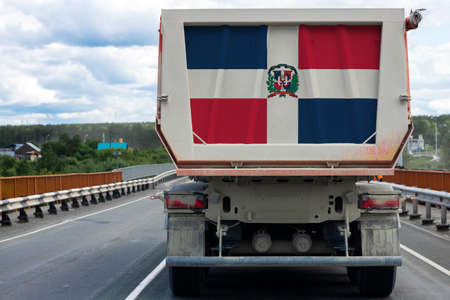 Big  truck with the national flag of Dominicana moving on the highway, against the background of the village and forest landscape. Concept of export-import,transportation, national delivery of goods