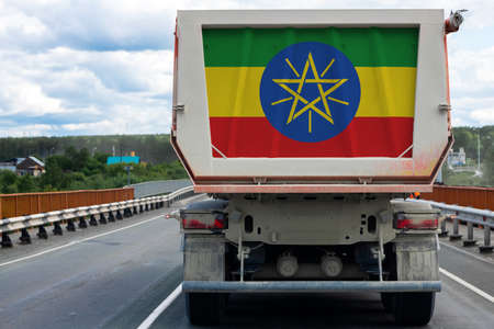 Big  truck with the national flag of Ethiopia moving on the highway, against the background of the village and forest landscape. Concept of export-import,transportation, national delivery of goods
