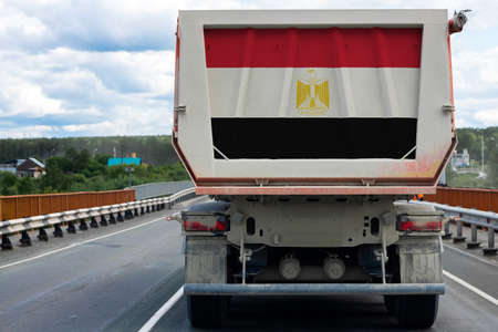 Big  truck with the national flag of  Egypt moving on the highway, against the background of the village and forest landscape. Concept of export-import,transportation, national delivery of goods  Фото со стока