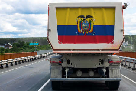 Big  truck with the national flag of  Ecuador moving on the highway, against the background of the village and forest landscape. Concept of export-import,transportation, national delivery of goods Фото со стока - 150593221