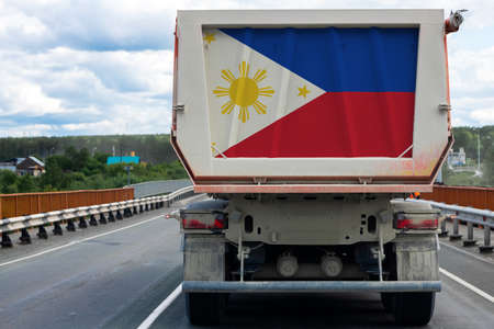 Big  truck with the national flag of  Philippines moving on the highway, against the background of the village and forest landscape. Concept of export-import,transportation, national delivery of goods